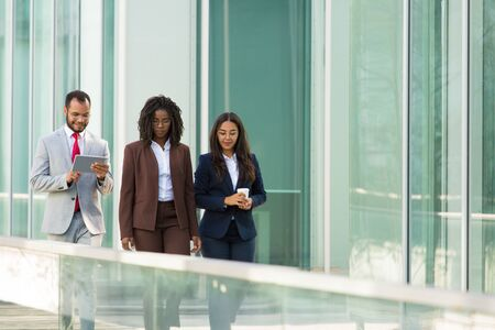 Three pensive colleagues going along outdoor office glass wall. Business man and women walking outside, using tablet, drinking takeaway coffee. Coffee break concept Stockfoto