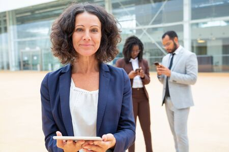 Joyful businesswoman holding tablet, posing outside and smiling at camera. Business man and woman using mobile phones behind her. Business lady with tablet concept