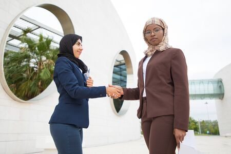 Confident Muslim businesswomen meeting outside. Business women in hijabs standing outdoors, looking at camera and shaking hands with each other. Muslim business lady concept