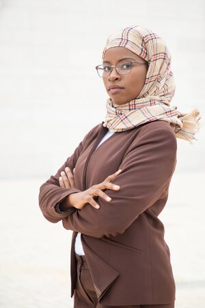 Confident Muslim female professional posing outside. Young dark skinned business woman in hijab and office suit standing for camera with arms folded. Muslim professional concept