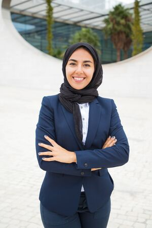Happy successful Muslim businesswoman posing outside. Beautiful young business woman in black hijab and office suit standing for camera with arms folded and smiling. Muslim business lady concept Фото со стока