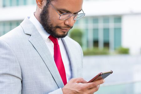 Focused serious businessman texting message on smartphones outside. Young Latin business man using mobile phone, office building in background. Digital gadget concept