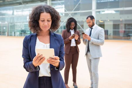 Positive businesswoman watching content on tablet outside. Business man and woman using smartphones behind her. Digital technology outdoors concept 写真素材