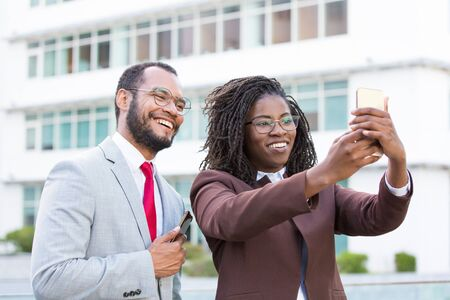 Happy business colleagues taking selfie outside. Business man and woman holding smartphone, posing and smiling at screen. Corporate friendship concept Stockfoto