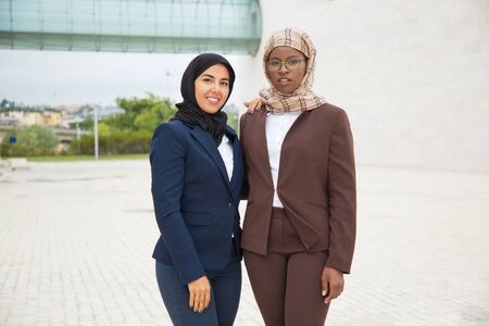 Successful proud female business team posing outside. Muslim women in hijabs and office suits standing close to each other, looking and smiling at camera. Muslim business team concept Фото со стока