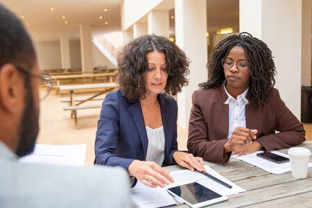 Ernsthafte weibliche Fachleute, die während des Treffens Vereinbarungsbedingungen besprechen. Geschäftsmann und Frauen sitzen am Café-Tisch mit Papieren und Geräten und reden. Firmenmeeting-Konzept Standard-Bild
