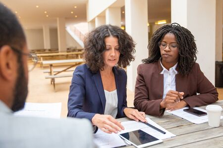 Serious female professionals discussing agreement terms during meeting. Business man and women sitting at cafe table with papers and gadgets and talking. Corporate meeting concept 版權商用圖片