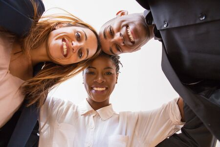 Happy diverse business team having fun and posing for camera. Low angle view of business man and women standing in circle, looking down and smiling. Low angle view concept