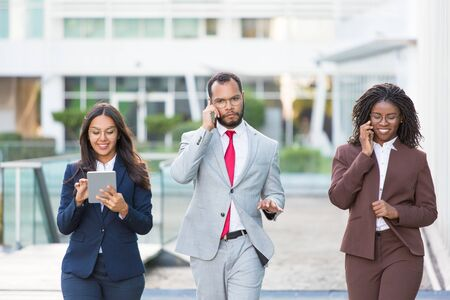 Multiethnic business team with gadgets going along urban glass facade. Business man and women walking outside, using tablet, talking on phone. Teamwork and communication concept Stockfoto