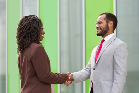Business partners greeting each other near office. Business man and woman standing outside and shaking hands with each other. Partnership concept