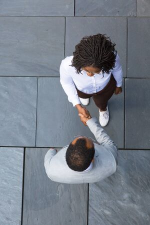 Business colleagues greeting each other near office. Top view of business man and woman standing outside and shaking hands with each other. Deal or partnership concept