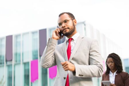 Serious Latin businessman speaking on cell while walking down city street. Confident man in office suit talking on cellphone, city building and passerby in background. Digital technology concept 写真素材