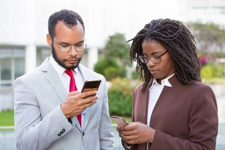 Diverse business colleagues using smartphones outside. Business man and woman texting message on cellphone, using online mobile app. Phone using concept