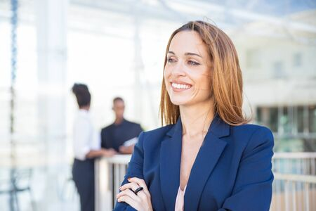 Happy successful businesswoman posing in office interior. Middle aged business woman standing for camera with arms folded, looking away and smiling. Business portrait concept Stock fotó