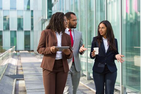 Team of diverse colleagues on their way to office. Business man and women walking outside, holding tablet, coffee cup and talking. Business group concept Stockfoto