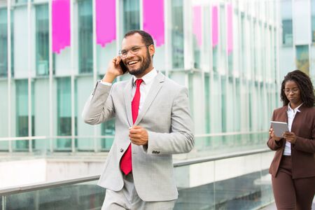 Cheerful Latin businessman talking on mobile phone while going down city street. Confident man in office suit calling on cell, woman with tablet walking behind him. Downtown area concept