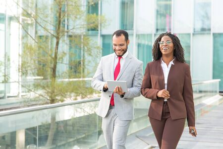 Cheerful coworkers discussing work issues outside. Business man and woman walking near office building, using tablet, talking, smiling, laughing. Walking businesspeople concept Stockfoto