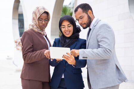 Excited diverse business colleagues watching presentation on tablet outside. Businessman and Muslim businesswomen standing outdoors and using tablet together. Interaction concept