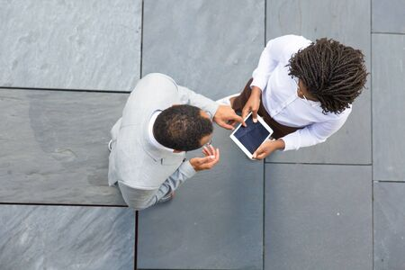 Two colleagues discussing project near office. Top view of business man and woman standing outside, talking and using tablet together. Teamwork concept Stockfoto