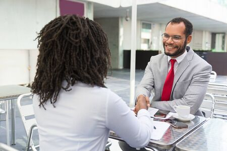 Employer welcoming applicant to team. Business man and woman meeting in street cafe and shaking hands with each other. Job interview concept