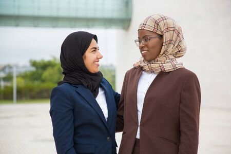 Happy confident female business team posing outside. Muslim women in hijabs and office suits standing for camera and hugging. Corporate friendship concept