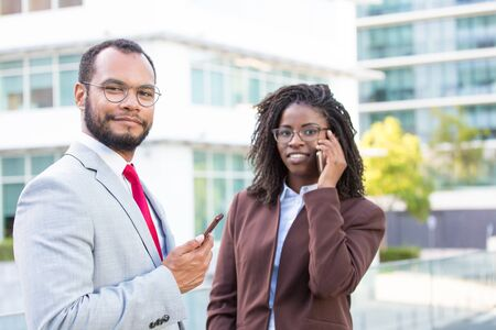 Multiethnic business team using smartphones outside. Business man and woman holding cellphone and talking on phone. Digital gadget using concept