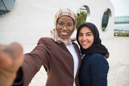 Joyful female corporate friends taking selfie outside. Muslim business women in hijabs holding mobile phone, hugging each other, posing and smiling at screen. Business and friendship concept