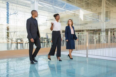 Real estate agent showing office building interior to customers. Business team of three walking through office hallway and talking. Business discussion concept