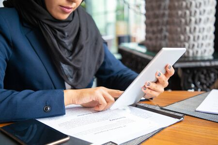 Businesswoman reading contract and consulting internet. Young Muslim business woman sitting in cafe, reading papers and using tablet. Digital communication concept