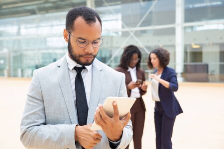 Serious businessman using tablet outside office building. His female business colleagues using mobile phones behind him. Communication outside concept