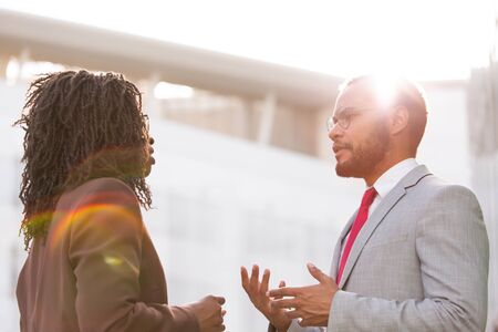 Serious colleagues talking and arguing outside. Business man and woman standing in business district against sunset light and discussing work issues. Business relationship concept Stockfoto