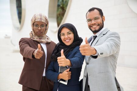 Multicultural business group posing and making like gesture. Businessman and Muslim businesswomen standing outdoors, showing thumb up and smiling at camera. Successful business team concept Imagens