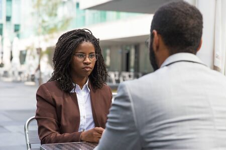 Customer consulting professional in outdoor cafe. African American businesswoman talking to business colleague, sitting at table, listening to him. Consulting concept