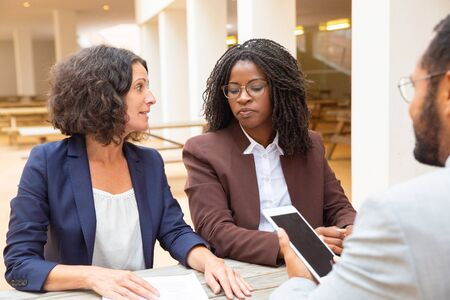 Diverse business partners meeting in office lobby. Business man and women sitting at table in cafe, discussing documents, using tablet. Business meeting concept