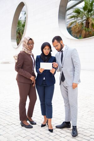 Diverse business group watching content on tablet outside. Businessman and Muslim businesswomen standing outdoors and using tablet together. Wireless technology concept Reklamní fotografie