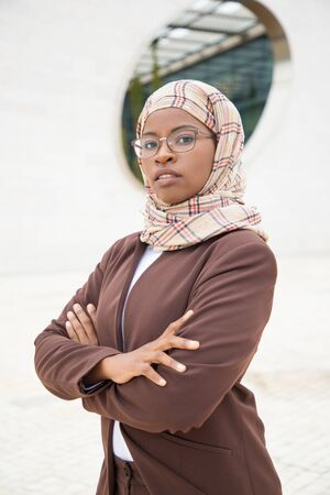 Serious successful Muslim business lady posing outside. Young dark skinned business woman in hijab and office suit standing for camera with arms folded. Muslim women in business concept Фото со стока