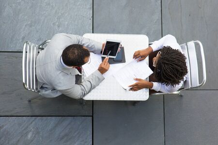 Two business colleagues reading and checking documents outside. Top view of business man and woman meeting in street cafe, working with papers, pointing at tablet screen. Business conversation concept