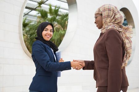 Happy Muslim business colleagues meeting outside. Business women in hijabs standing outdoors, looking at camera and shaking hands with each other. Merger concept