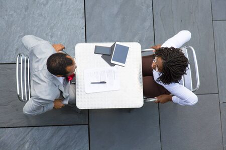 Business colleagues finishing meeting in street cafe. Top view of business man and woman sitting at table with papers and gadgets and ready to stand up. Closing deal concept Stockfoto