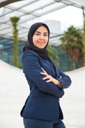 Successful proud Muslim business lady posing outside. Portrait of young business woman in black hijab and office suit standing for camera with arms folded. Muslim businesswoman concept Фото со стока