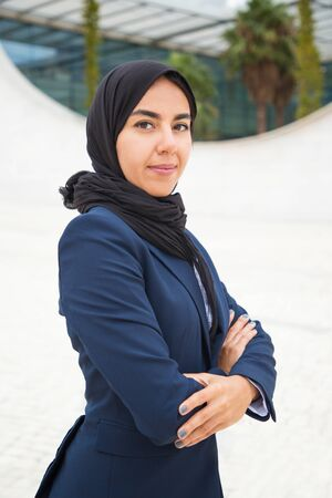 Confident proud Muslim businesswoman posing outside. Beautiful young business woman in black hijab and office suit standing for camera with arms folded. Muslim professional portrait concept