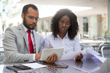 Focused coworkers checking reports on papers and on tablet. Business man and woman sitting in coffee shop, showing tablet and smartphone screens to each other. Teamwork concept