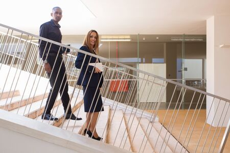 Two multiethnic coworkers posing on their way from office. Business man and woman walking down stairs, carrying tablets and looking at camera. Corporate communication concept Stockfoto