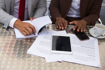 Business partners discussing agreement in outdoor cafe. Closeup of business man and woman sitting at table with papers, gadgets and writing notes. Deal concept