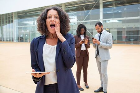Excited businesswoman with tablet getting great shocking news. Business man and woman using smartphones behind her. Digital device using concept