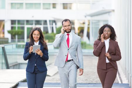 Diverse business colleagues with gadgets going along urban glass facade. Business man and women walking outside, using tablet, talking on phone. Team and digital technology concept Stockfoto
