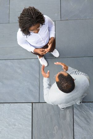 Two coworkers accidently meeting and talking near office. Top view of business man and woman standing outside, discussing project and gesturing. Business communication concept