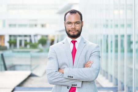 Confident businessman posing outside with folded arms. Handsome young Latin business man wearing eyeglasses and red tie and looking at camera. Successful businessman concept