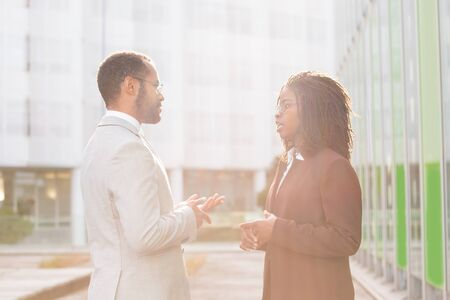Multiethnic business team discussing project near office building. Business man and woman standing outside and talking. Business relationship concept Stockfoto