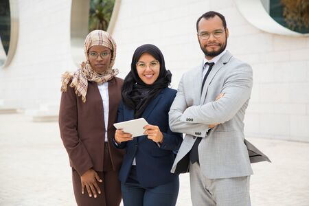 Successful interracial business team with tablet posing outside. Businessman and Muslim businesswomen standing outdoors, holding tablet and looking at camera. Diverse colleagues conce